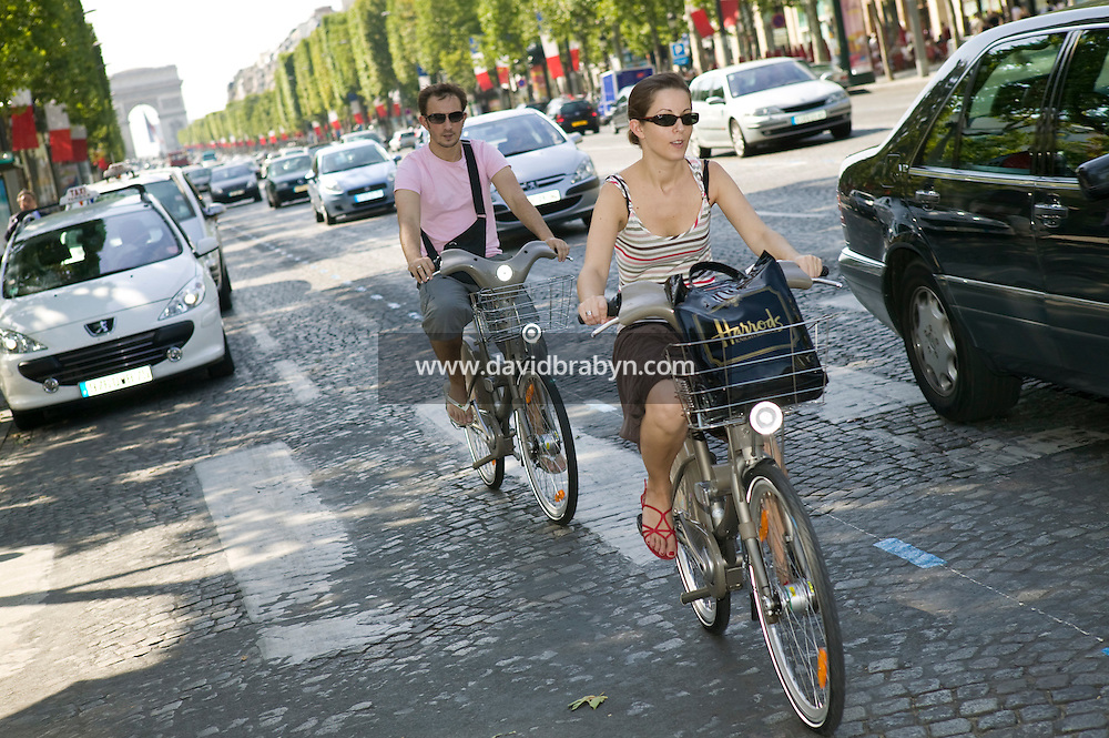 A couple rides their Velib' bicycles down the Champs-Elysees in Paris, France, 15th July 2007. The city of Paris launched this low-cost self-service bicycle system today with a fleet of 10,000 bicycles.