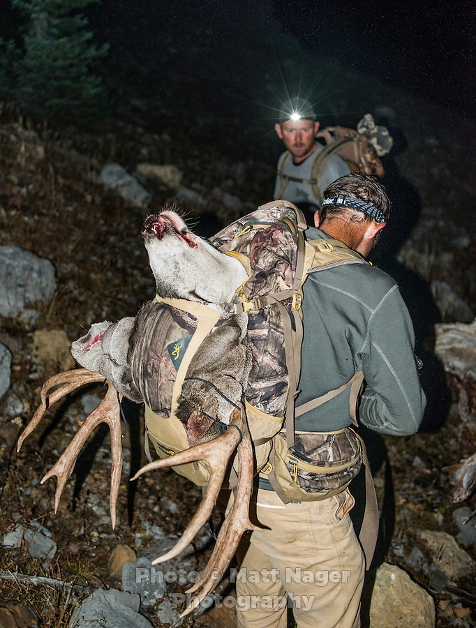 Outdoor Life Editor Andrew McKean carries his trophy antlers from a mule deer hunt with Greg Kriese of Trefren Outfitters looking on at Greyback Ridge in the Hoeback Drainage of Wyoming Region H, outside of Alpine, Wyoming, September 21, 2015.<br /> <br /> Photo by Matt Nager