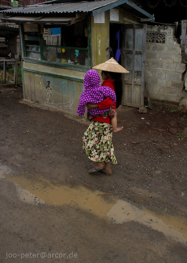 child with baby walking along the street after rain, village  Nyaungshwe close to  Inle Lake, Shan state,  Myanmar,