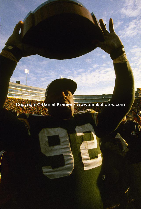 """Green Bay Packers defensive end Reggie White hoists the George Halas Trophy as the Green Bay Packers defeated the Carolina Panthers 30-13 on January 12, 1997 in the NFC championship game at Lambeau Field. This was the first title game in Green Bay since the """"Ice Bowl"""" in 1967."""