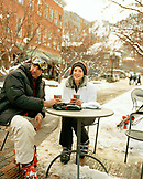 USA, Colorado, Aspen, couple wearing ski gear having coffee at an outdoor table in the Winter in downtown
