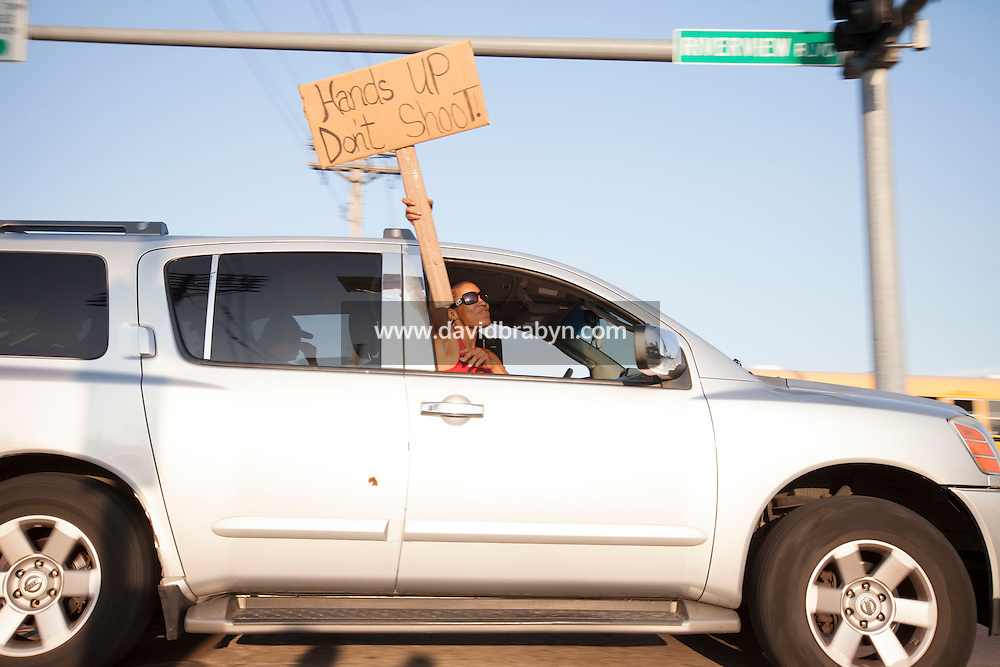 HSUL 20140819 United States, St Louis, MO. A woman holds up a sign that reads 'Hands up, Don't Shoot', as she rides in a car where St. Louis police say officers shot and killed a 23-year-old man who was wielding a knife and refused to drop it on August 19, 2014 in St Louis, Missouri. Photographer: David Brabyn