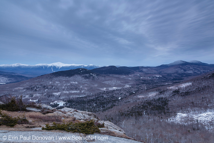 The Presidential Range at sunset from Middle Sugarloaf Mountain in Bethlehem, New Hampshire on cloudy winter day.
