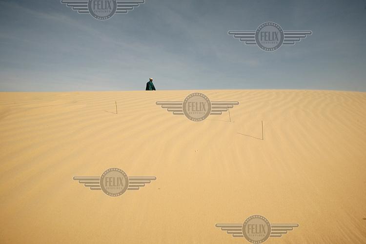 A man walks over a sand dune near Damasak.