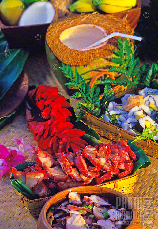 Succulent local-style luau food delights in woven baskets and bowls set on lauhala mat. Sushi, kalua pork, poki and tropical fruits with red torch ginger, orchid blossom and fern decor.