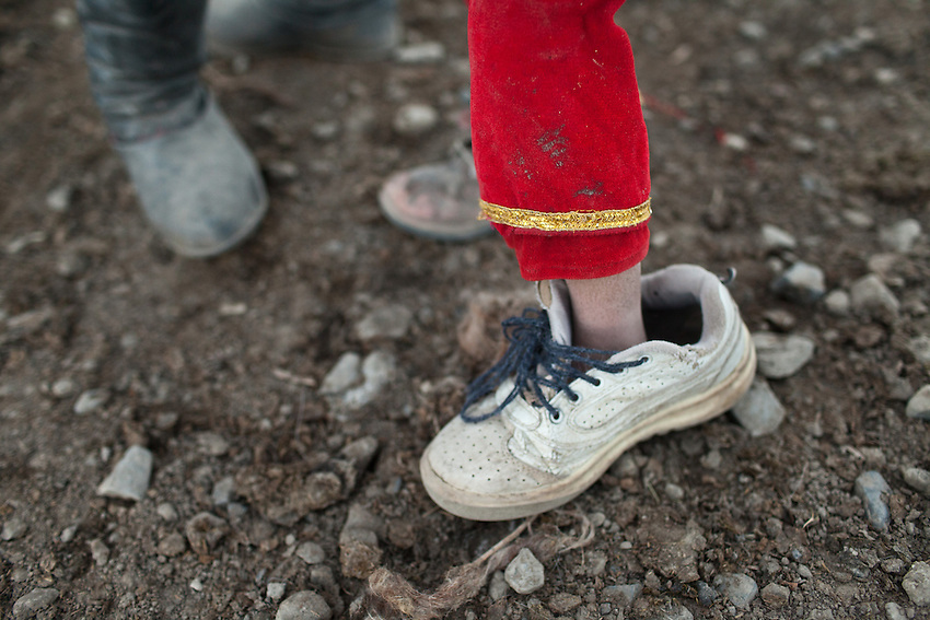 A Kyrgyz girl wears her big brother's shoe. The next shop is about a 3 weeks round trip on horse back. At the Kyrgyz settlement of Bozoi Gumbaz, before Chaqmaqtin lake, Amon Boi's camp...Trekking through the high altitude plateau of the Little Pamir mountains (average 4200 meters) , where the Afghan Kyrgyz community live all year, on the borders of China, Tajikistan and Pakistan.