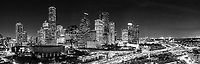 Aerial Houston Skyline BW Pano - An black and white aerial view of the Houston Skyline after dark taken using our S900 drone.  This angle show the Houston Aquarium with the purple ferris wheel and the colorful city hall in a rainbow of colors as the high rise buildings light up along IH45 in downtown.  You can also see all the many skycrapers near the Theater District in the city .  Houston is know for having many cultural events and this area has museums,, art, theater, plays , opera, and many music event along with the Aquarium. Houston is the most populous city in Texas and fourth most populous in the US currently the population is 3.4 million as of the 2016 census.