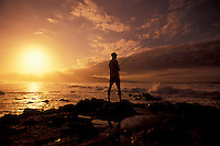 The sun sets over the West Maui Mountains with a local fisherman silhouetted at Hookipa, Maui.