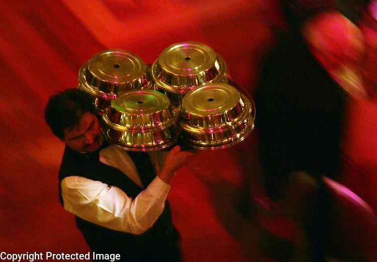 A waiter delivers a tray full of entrees while walking across the dance floor in the main dining area during the 2006 Symphony Ball benefiting the Nashville Symphony at the Schermerhorn Symphony Center in Nashville, Tenn.,  Saturday, Dec. 9, 2006.&amp;#xD;Jeff Adkins /for The Tennessean<br />