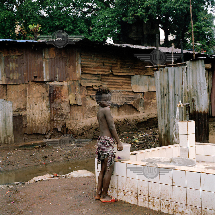 A young girl waits to collect water from a pump in Kroo Bay. Kroo Bay, a slum built on a rubbish dump on the eastern outskirts of the capital Freetown, houses around 6,500 people. The rubbish that is washed down the hill from the city toward Kroo Bay is compacted in the bay to the extent that houses can be built on the surface, thus reclaiming land from the sea.