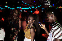 ACCRA, GHANA APRIL 18: Young people enjoy themselves in a club on April 18, 2015 in Accra, Ghana.  Many of the customers in this club are involved in Romance scams, credit card fraud and etc. The country is a center for different online scams. Both men and women are lured to send cash to someone they only met on the net.  Due to limited opportunities, many youngsters spend their days in Internet cafes trying to scam people form all over the world. (Photo by: Per-Anders Pettersson)