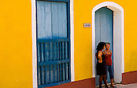 Two local women talking in doorway against bright yellow wall of building of the old colonial city of Trinidad in Cuba