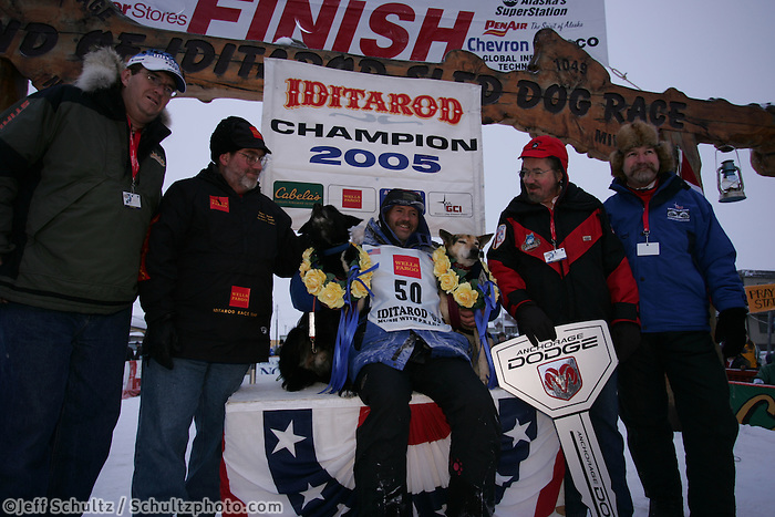 "Robert Sorlie and his two lead dogs ""Sox"" and ""Blue"" are surrounded by representatives from the major sponors of the Iditarod at the finish line in Nome.  End of the  2005 Iditarod Trail Sled Dog Race."