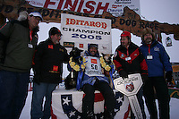"""Robert Sorlie and his two lead dogs """"Sox"""" and """"Blue"""" are surrounded by representatives from the major sponors of the Iditarod at the finish line in Nome.  End of the  2005 Iditarod Trail Sled Dog Race."""