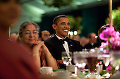 Washington, DC - November 24, 2009 -- United States President Barack Obama smiles while watching the entertainment at the State Dinner for Prime Minister Manmohan Singh of India and his wife, Mrs. Gursharan Kaur, held in a tent on the South Lawn of the White House, November 24, 2009..Mandatory Credit: Pete Souza - White House via CNP