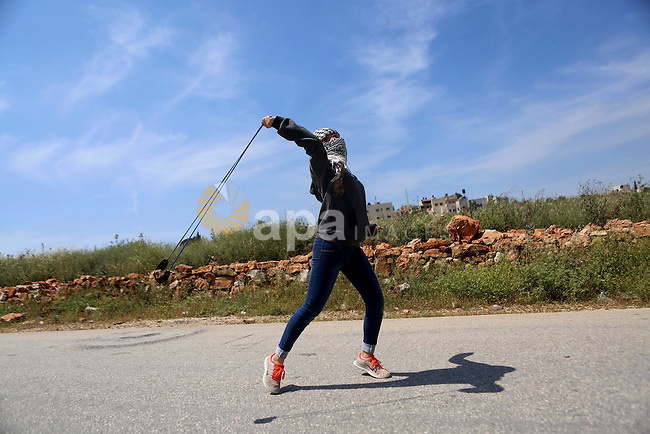 A Palestinian girl uses a slingshot to hurl stones towards Israeli security forces during clashes following a march against Palestinian land confiscation on April 15, 2016 in the West Bank village of Nabi Saleh near Ramallah. Photo by Shadi Hatem
