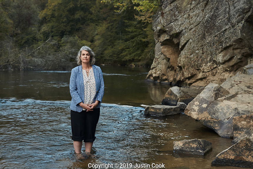 Portrait of Caroline Armijo at Moratock State Park on the Dan River in Danbury, North Carolina, Saturday, October 12, 2019 . In 2014, a leak from a Duke Energy site left coal ash coating 70 milesof the Dan River on the North Carolina-Virginia border. Caroline Armijo is environmental advocate and artist who now lives in Greensboro, North Carolina, but grew up in Stokes County where the coal ash spill took place. Her work incorporates her concern for environmental issues threatening her home community – coal ash and fracking. She advocates with Residents for Coal Ash Clean Up, which supports the Belews Creek Community and Alliance of Carolinians Together (ACT) against Coal Ash. (Justin Cook)