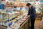 """Munehiro Ueda arranges items of replica food at his store """"Maizuru"""" in Kappabashi district, in Tokyo, Japan on Nov. 10 2010. Often called Tokyo's Kitchen Town, stores in Kappabashi still mainly caters to professionals in the catering industry, though is becoming increasingly popular with foreigners hunting for unique souvenirs..Photographer: Robert Gilhooly"""