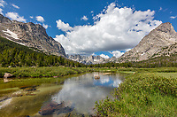 Wind River Range, WY: Blue sky reflections in the Popo Agie River with the profile of the Cirque of the Towers in the distance; Bridger Wilderness in the Bridger National Forest in summer