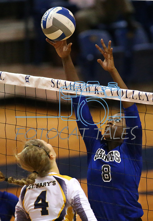 Marymount's Morgan McAlphin blocks a hit from St. Mary's College during a college volleyball game in Lexington Park, MD, on Wednesday, Oct. 29, 2014. Marymount won 3-2 to go 24-9 on the season.<br /> Photo by Cathleen Allison