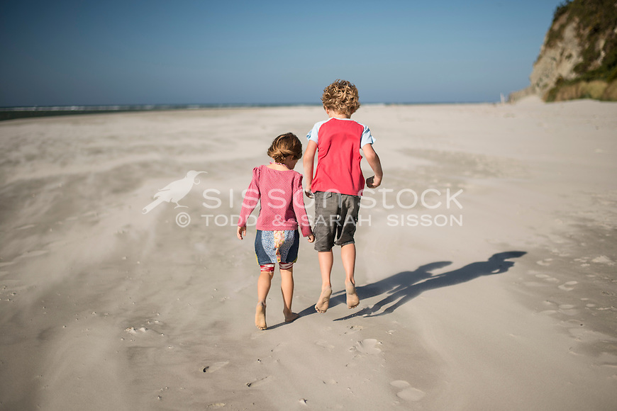 Young boy and girl playing on the beach at Doctors Point, near Dunedin, Otago, New Zealand - stock photo, canvas, fine art print