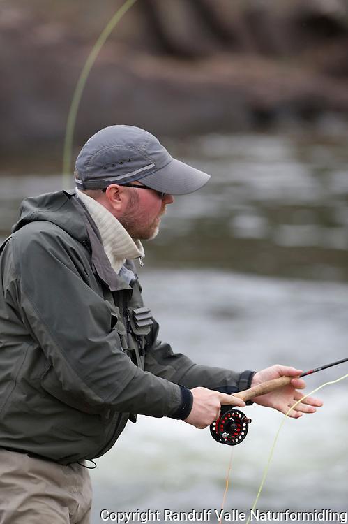Fisker i Repparfjordelva. ---- Angler in Repparfjordelva in Finnmark.