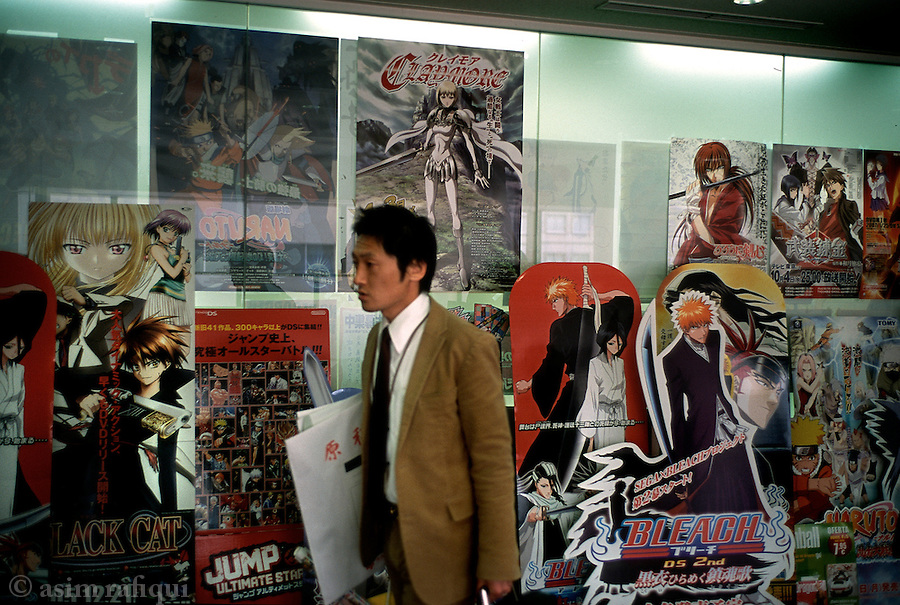 In the offices of the popular manga magazine Shonen Jump, decorated with posters and placards depicting popular manga comic characters.