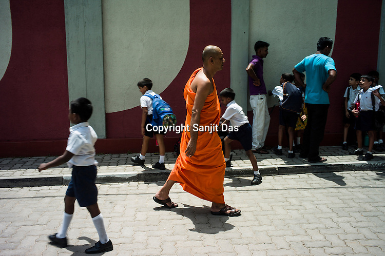 School children stop to take blessings from a Busshist monks outside a school in Colombo, Sri Lanka.  Photo: Sanjit Das/Panos