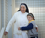 Sister Anahid, a member of the Dominican Sisters of St. Catherine of Siena, gets a hug from a student in a primary school she supervises in Dohuk, Iraq. Most of the students were displaced from their home villages when the Islamic State group took over portions of the Nineveh Plains in 2014. Because they came from communities with Arabic curriculum schools, they often don't fit well in schools in the villages where they resettled, because those schools teach in Kurdish or Assyrian. So the religious order started the school, which has students from several faiths, including Islam and Christianity. The Christian Aid Program Nohadra - Iraq (CAPNI) provides transportation for many students to Dohuk from the rural villages where their families have taken refuge.