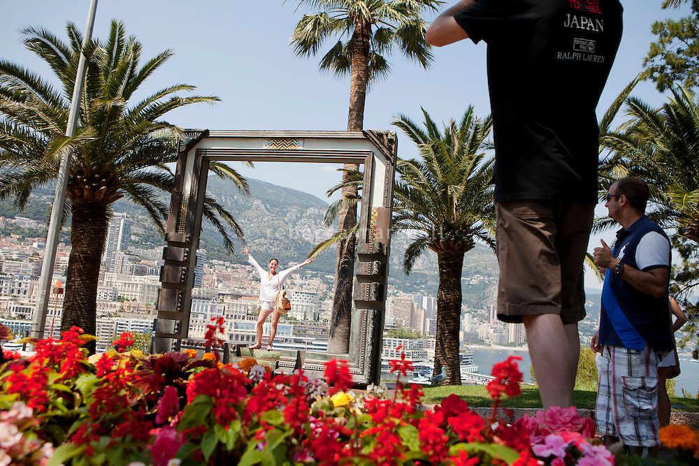 Tourists photograph each other posing on a sculpture by artist Nall in gardens on Le Rocher, Monaco, 6 July 2013. Port Hercule and the hill of Monte Carlo can be seen in the background.
