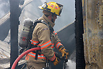 A firefighter spraying water on a structure fire hotspot