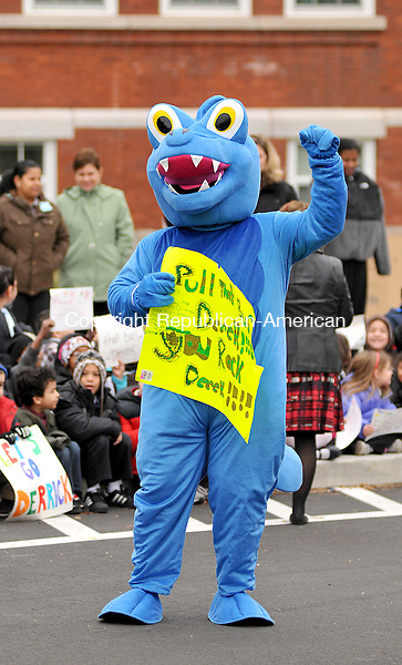 WATERBURY, CT, 22 NOVEMBER 2011-112211JS03-The  Diggan Dragon, the mascott for Duggan Elementary School in Waterbury, cheers on Derek Poundstone, the strongest man in America as he pulls a school bus filled with donated food collected by student and staff at the school on Tuesday. The food will be donated to local families, the Salvation Army and a local church. <br />  Jim Shannon Republican-American