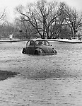 A Volkswagen sits in the flooded parking lot of Royal Crest apartments on Sharon Road, inundated by the fast-rising waters of the Mad River, March 1980 in Waterbury.