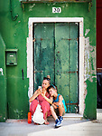 A woman and her son check their smart phone, sitting in the shade in front of a green door in the colorful village of Burano, Italy.