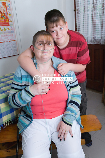 Young carer with his arm around his mum; who is severely asthmatic; who he looks after,