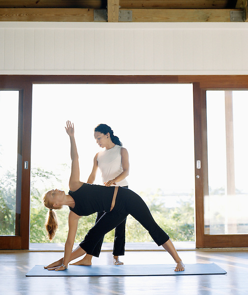 PARROT CA,TURKS AND CAICOS : A yoga instructor helps a student during a yoga class at Parrot Cay resort. Turks and Caicos, British West Indies.