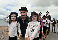 28-8-2011:  Local celebrity Mick O'Dwyer with Lia Clancy and Katie Malone as he leads 108 Charlie Chaplin lookalikes down Waterville promenade on Sunday as they set a new world record on the concluding day of the Charlie Chaplin Film Festival. The previous record of 88 was easily achieved as babies and pensioners dressed up like Charlie Chaplin to make history.<br /> Picture by Don MacMonagle