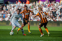 SWANSEA, WALES - APRIL 04: Gylfi Sigurosson ( left ) of Swansea City  in action during the Premier League match between Swansea City and Hull City at Liberty Stadium on April 04, 2015 in Swansea, Wales.  (photo by Athena Pictures)
