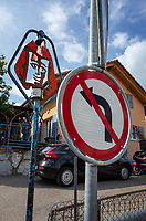 Switzerland. Canton Fribourg. Neyruz. Traffic sign. No left turn. A metal sculpture by the artist Xavier Vimal, who stands in the courtyard of his private house. The art piece is dedicated to  the artist Jean Tinguely, who is buried in the village. Jean Tinguely (22 May 1925 – 30 August 1991) was a Swiss sculptor. He is best known for his sculptural machines or kinetic art, in the Dada tradition; known officially as metamechanics. Tinguely's art satirized the mindless overproduction of material goods in advanced industrial society. 21.05.2019 © 2019 Didier Ruef