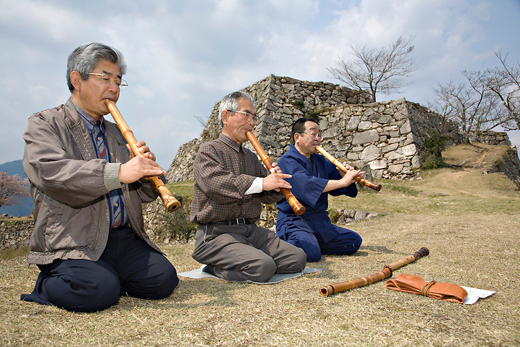 Three men playing Shakuhatchi, a traditional Japanese bamboo flute at Takeda Castle