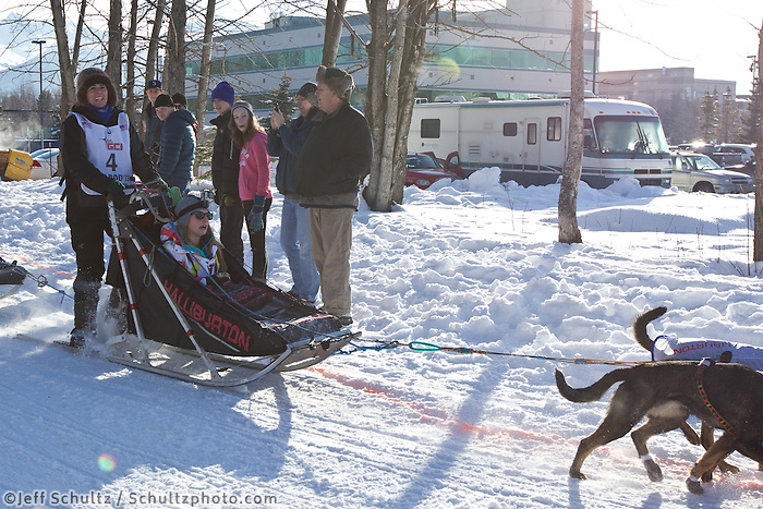 Jodi Bailey and team run past spectators on the bike/ski trail during the Anchorage ceremonial start during the 2013 Iditarod race.    Photo by Britt Coon/IditarodPhotos.com