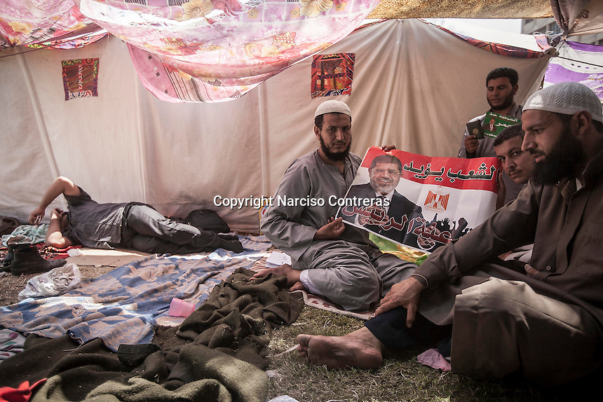 In this Saturday, Jul. 06, 2013 photo, Muslim Brotherhood members sit inside a tent as they show a banner of the ousted president Morsi after clashes early moring with members of the opposition nearby to the Cairo University in Egypt. (Photo/Narciso Contreras).