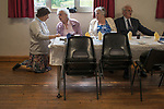 Priddy Friendly Society annual Club Walk Day. Somerset Uk 2019. In the village hall  before lunch is served the rector of the Church of St Lawrence, Priddy, the Revd. Paula Hollingsworth is on her knees listening and talking to elderly members of the community.