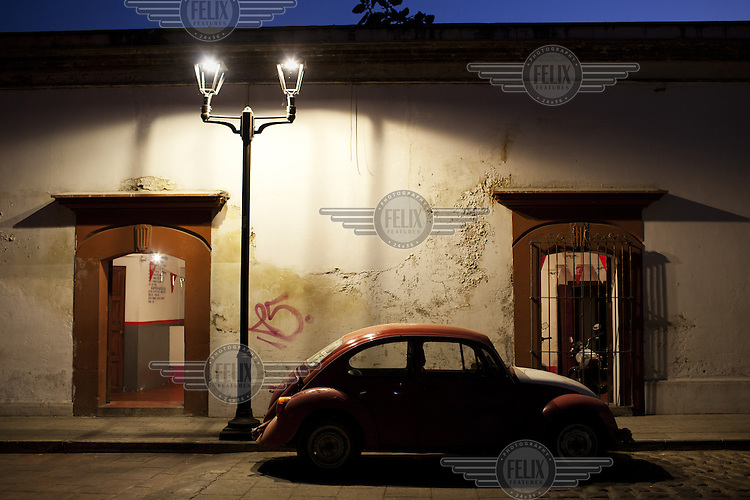 A Volkswagen Beetle parked beneath a street lamp. The original Beetle was widely popular in Mexico and was still produced there until 2004.