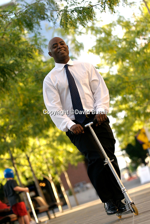 African American businessman riding scooter