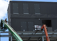 NWA Democrat-Gazette/ANDY SHUPE<br /> Randy Peterson and Juan Badillo, both workers with Southern Bleachers in Graham, Texas, work Wednesday, Aug. 12, 2015, to assemble a new press box atop the stands at Harmon Stadium at the school. The structure still lacks one more story, an upper level that will house video photographers and utilities.