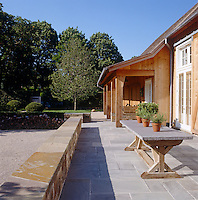 The elegant bluestone terrace to the rear of the barn has a stone-topped trestle table and a low wall for sitting upon