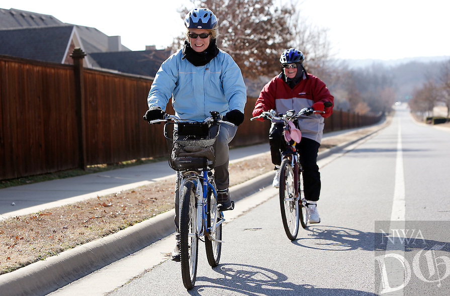 NWA Democrat-Gazette/DAVID GOTTSCHALK - 2/11/15 - Joy Williams (left) and Nancy Fuller, both of Fayetteville, make their way up the hill in the bike lane on Vantage Drive in Fayetteville Wednesday February 11, 2015. The two, still dressed warm because of the wind, ride regularly and were traveling on an 11.5 mile loop which would take them back through Johnson.