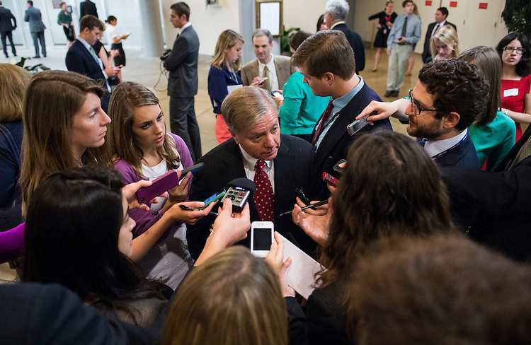 UNITED STATES - JUNE 11: Sen. Lindsey Graham, R-S.C., speaks with reporters as he makes his way from the Senate subway to the Capitol for the weekly policy lunch on Tuesday, June 11, 2013.  (Photo By Bill Clark/CQ Roll Call)
