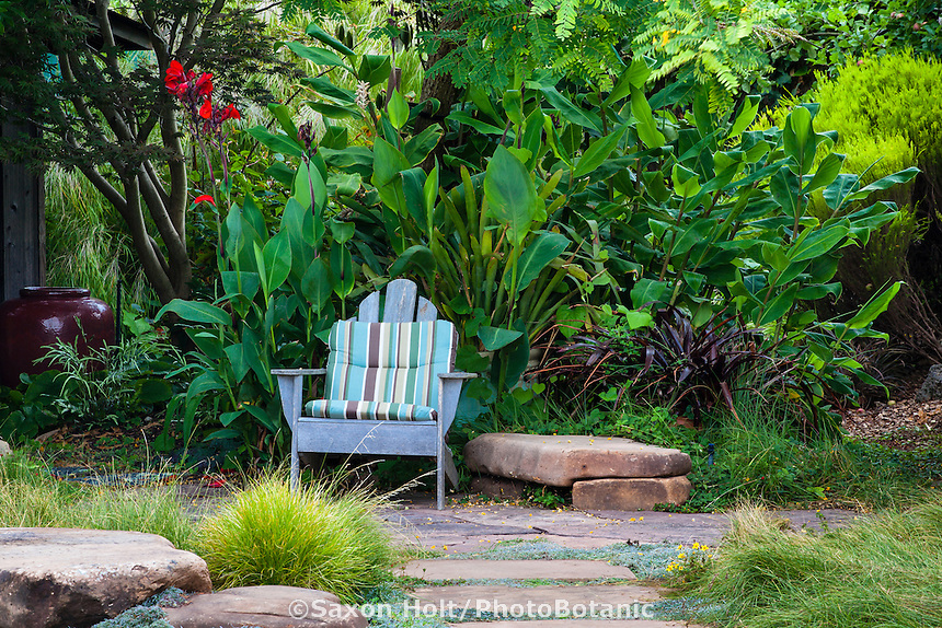 Cushioned adirondack chair by stone bench and path in backyard garden design by plant collector Sherry Merciari